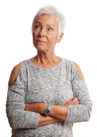unsmiling: unsmiling mature woman with arms folded looking away. isolated on white.