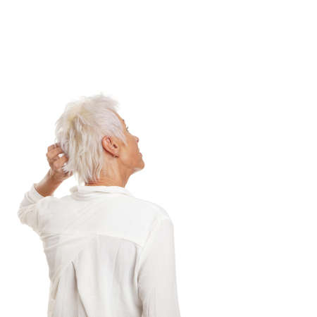 puzzled older woman scratching her head and looking up to copy space Stockfoto