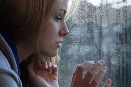 sad young woman looking through window on rainy day. depression concept. Standard-Bild
