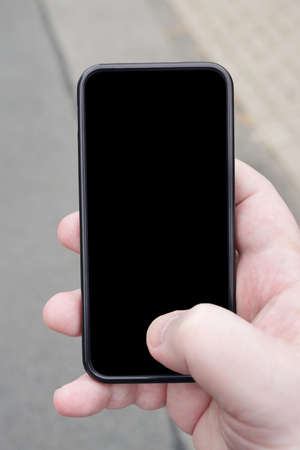 personal perspective: hand holding smartphone with blank screen from personal perspective