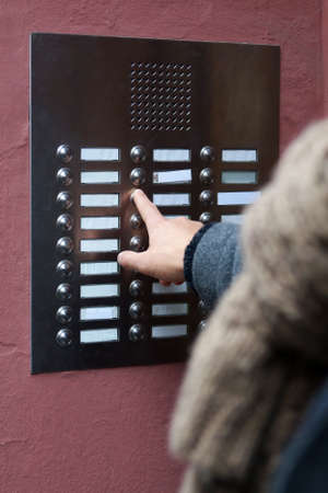 interphone: unrecognizable person ringing doorbell at apartment building. many blank nameplates.