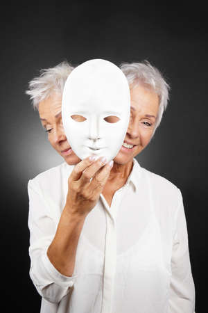 hypocrisy: older woman hiding happy and sad face behind mask, concept for manic depression or bipolar or dramedy comedy drama Stock Photo