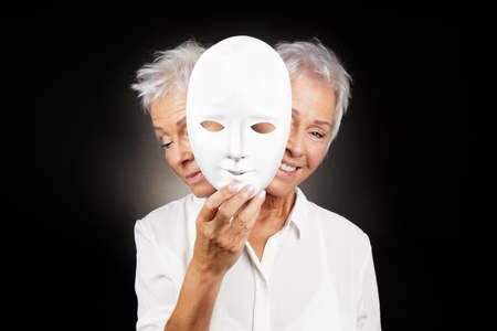 older woman hiding happy and sad face behind mask, concept for manic depression or bipolar or dramedy comedy drama Stockfoto