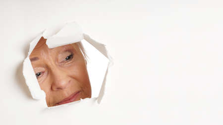 voyeur: curious older woman looking through hole torn in white paper background at copy space. panoramic 16:9 banner or header format.