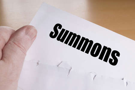 summons: hand holding summons letter, unrecognizable person is summoned to appear in court