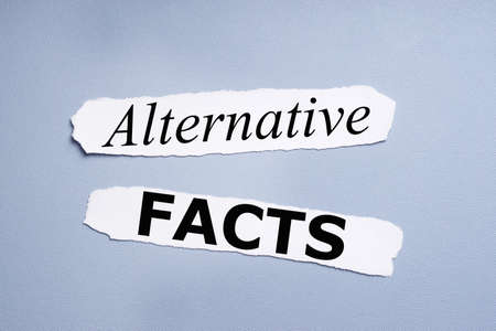 disinformation: alternative facts, phrase printed on pieces of paper over blue background Stock Photo