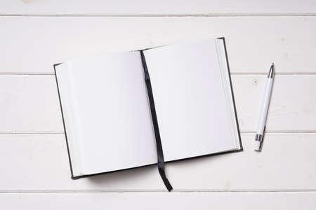ball pens stationery: Abra el cuaderno con las páginas en blanco y la pluma en el escritorio de madera blanco