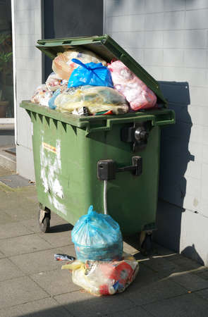 disposed: wheeled trash can container overflowing with garbage bags