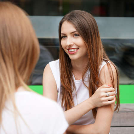 two young women talking to each other. girl friends having a chat. Stock Photo