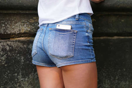close-up rear view of young woman wearing denim hot pants or booty shorts with smartphone in back pocket