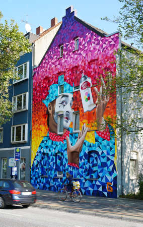 Hannover, Germany - September 21, 2017: Street art by international graffiti artists MrDheo and ParizOne sponsored by local building company Gundlach at the corner of Celler Str and Hamburger Allee.