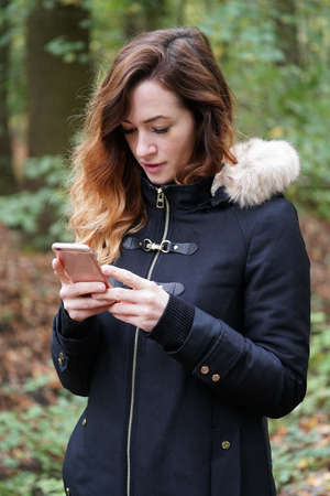 young woman using mobile or smartphone while outdoors in forest Stock Photo