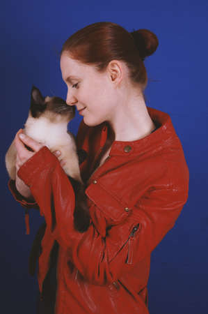 young woman wearing red leather jacket touching noses with her siamese cat