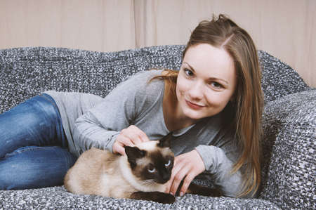 happy young woman relaxing on sofa with her siamese pet cat