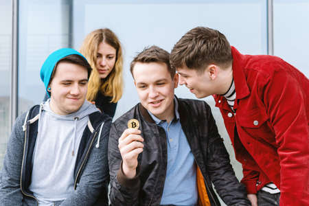 young man showing bitcoin coin to his intrigued group of friends, cryptocurrency hype concept Stock Photo