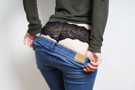 rear view of midsection of unrecognizable young woman undressing revealing bottom in black lace panties underneath blue jeans