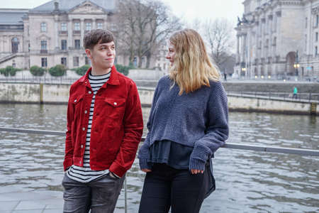 young woman and man hanging out by the river Spree in Berlin, Germany, with Bundestag Reichstag building in the background Reklamní fotografie