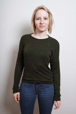 Three quarter length blue-eyed blonde confident young woman standing
