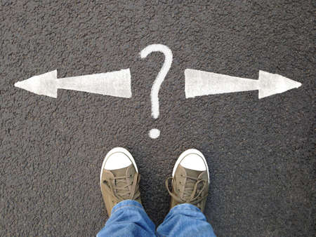 feet in canvas shoes standing on asphalt from personal perspective, road markings with arrows pointing left and right with question mark Stock Photo - 99867316