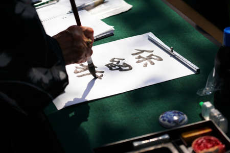 japanese calligraphy, unrecognizable person writing kanji characters (English translation: reserved) with ink brush on paper Archivio Fotografico