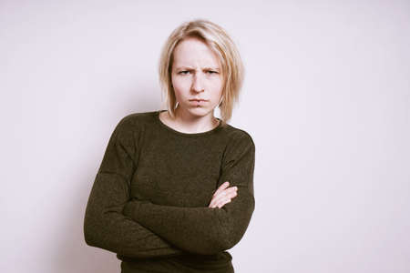 angry young woman frowning with arms crossed, negative emotion concept with copy space Stock Photo