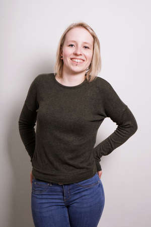 young blond millennial woman smiling, three quarter length real people portrait