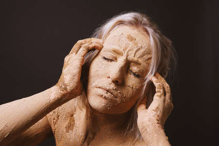 woman covered in dry cracked clay mud mask holding her head in pain Stock Photo