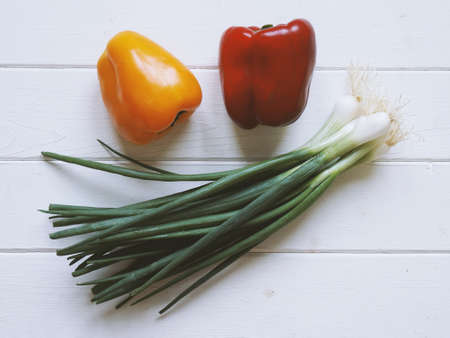 Sweet peppers and scallions, top view on white wooden table