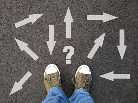 feet standing on asphalt with multitude of arrows in different directions and question mark, confusion choice chaos uncertainty concept
