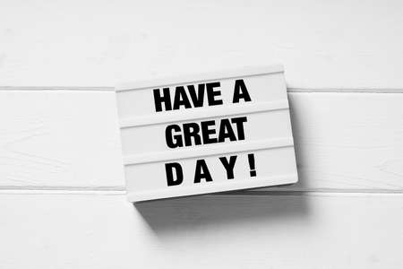 have a great day motivational text on light box light box sign on white wooden background Stock Photo