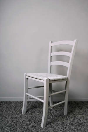 empty vacant chair in entirely gray room Stock Photo
