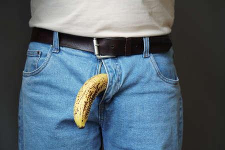 oude slappe hangende banaan die aan het genitale gebied van een geklede onherkenbare man hangt, impotentie erectiestoornissen of slap-lul concept