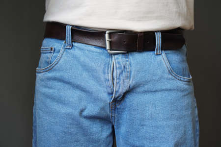 midsection of unrecognizable man dressed in jeans with open fly or flies or zipper Stockfoto