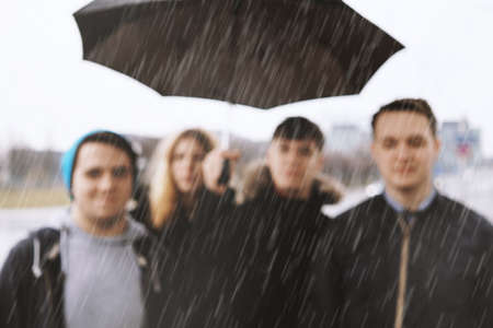 defocused group of young urban teenage friends under one umbrella in heavy rain - blurred background image with copy space - bad weather concept Stock Photo