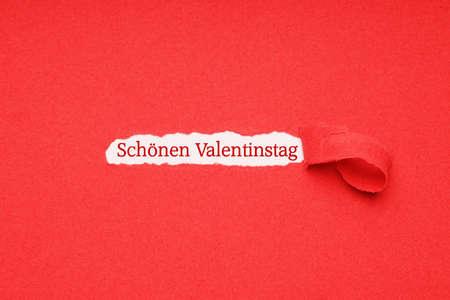 schonen valentinstag means happy valentines day in german - hidden message seen through hole torn in red paper background