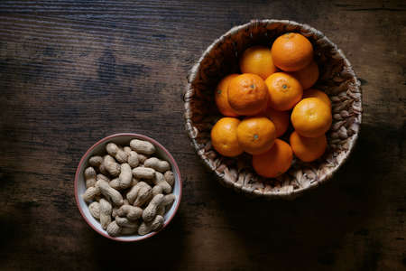 overhead top view of two bowls full of peanut nuts and clementine mandarin ornages on rustic wooden table Stock Photo