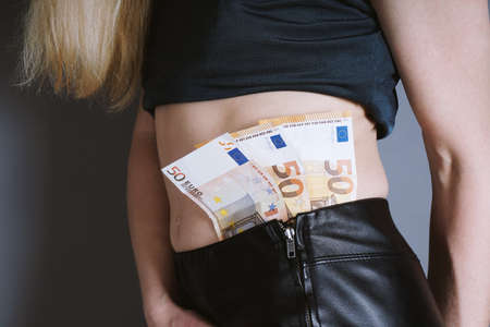 unrecognizable woman with euro bank notes in leather pants - stripper or prostitute cash payment concept