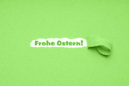 Frohe Ostern is German for Happy Easter - hole torn in green paper background to reveal easter greeting