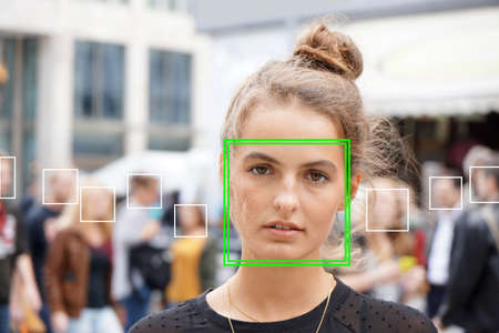 young woman picked out by face detection or facial recognition software - several other faces detected in crowd of people in background Stock Photo