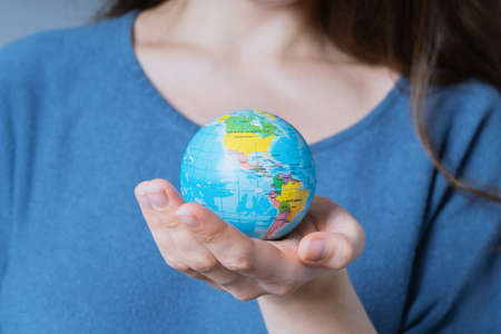 young unrecognizable woman holding world globe in her hands - travel or environmnetal protection concept