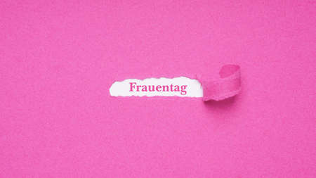 Frauentag is German for Womens Day which is celebrated on March 8 - text revealed by hole torn in pink paper background