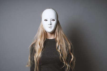 Mujer misteriosa que oculta el rostro y la identidad detrás de una máscara blanca lisa: falta de concepto de emoción Foto de archivo