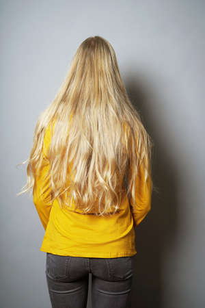 rear view of young woman with long blond hair standing facing wall