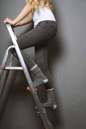 unrecognizable woman climbing ladder in socks - home improvement diy or household accident risk concept