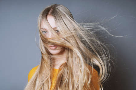 blond young woman with long windswept tousled hair blowing into her face