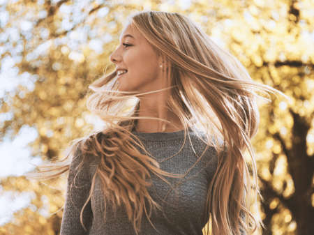 blond teenage girl shaking or flicking her hair - zest for life concept 스톡 콘텐츠