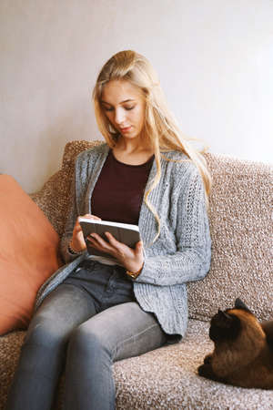 teenage girl using tablet computer at home while relaxing on sofa with cat - candid real people lifestyle