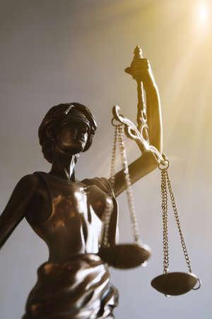 Lady Justice oder Justitia mit verbundenen Augen Figur, die Waage hält - Gesetz und Rechtssymbol - mit Sonnenstrahlen Lichtaustritt