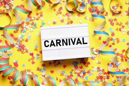 carnival flat lay with text on light box sign confetti and streamers