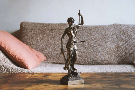 lady justice or justitia statue on table in living room - landlord and tenant law or right of residence concept